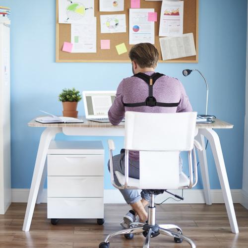 Using a posture corrector at a computer desk